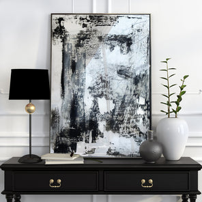 Abstract, mixed media painting on mirror, with black tones, in brass frame. Displayed on table, leaning up against the wall. Lamp placed to the left while vases are on the right of the mirror.