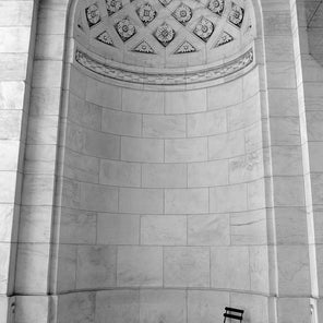 Black and white photograph of a marble rotunda with a fold out chair in the bottom, right hand corner.