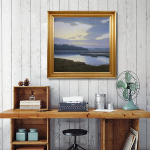 Robert Tinney's painting, Flight of Color, in a gold-hued frame, hanging on a white wood panel wall above a natural wood desk and black stool.
