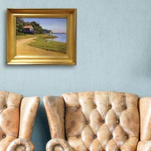 Robert Tinney's painting, Beach House, in a gold-hued frame, hanging on a light blue wall above two brown leather chairs.