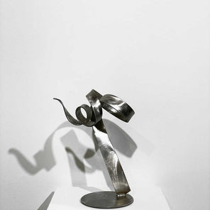 Stainless steel, abstract sculpture, from the front view, sitting on a pedestal in front of a white wall.