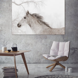 "Kimerlee Curyl's ""Dashing"" Hung on a grey concrete wall. Under the photograph is a white chair with a wooden base as well as a wooden table. A small round black and white area rug is placed at the foot of the chair."