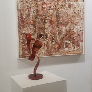 Abstract, steel sculpture with orange dye, sitting on a pedestal in front of an abstract painting.