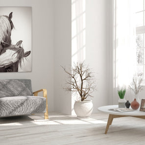 """Turtle Doves"" Staged in a living room with white walls. It has been hung over a grey armchair. To one side is a white round coffee table with wooden legs."