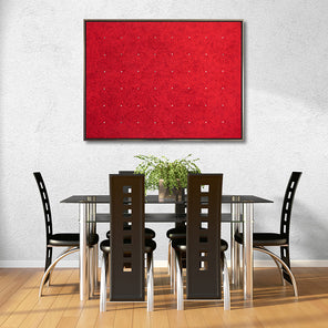A print of Ellie Winberg's artwork, Kind of Red, in a warm silver floater frame, hanging on a white wall above a black and silver dining set.