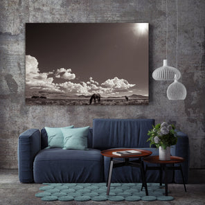 """Desert Sanctuary"" Staged on a dark grey wall above a navy blue couch with teal throw pillows. In front of the couch is two small round tables."