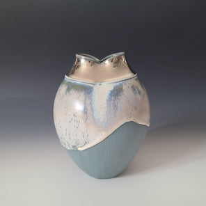 A blue textured sculptural vessel with light, multicolored glaze and a white mouth sitting on a gradient surface.