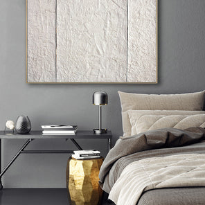 A print of Ellie Winberg's artwork, Pearl Wall Two, in a warm silver floater frame, hanging on a grey wall above a neutral tone bed and black nightstand.