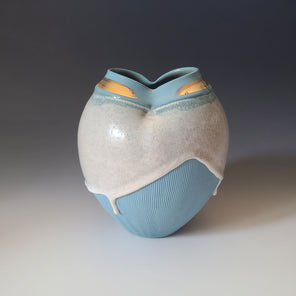 A textured blue ceramic sculptural vase with white, dripping glaze and and gold embellishment along the rim.
