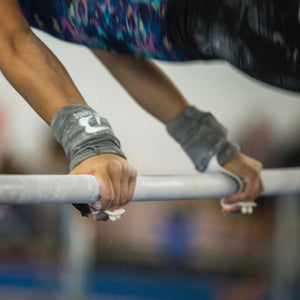 Gymnast with inverted grip using DRY bands to keep her grips from snagging on her clothes