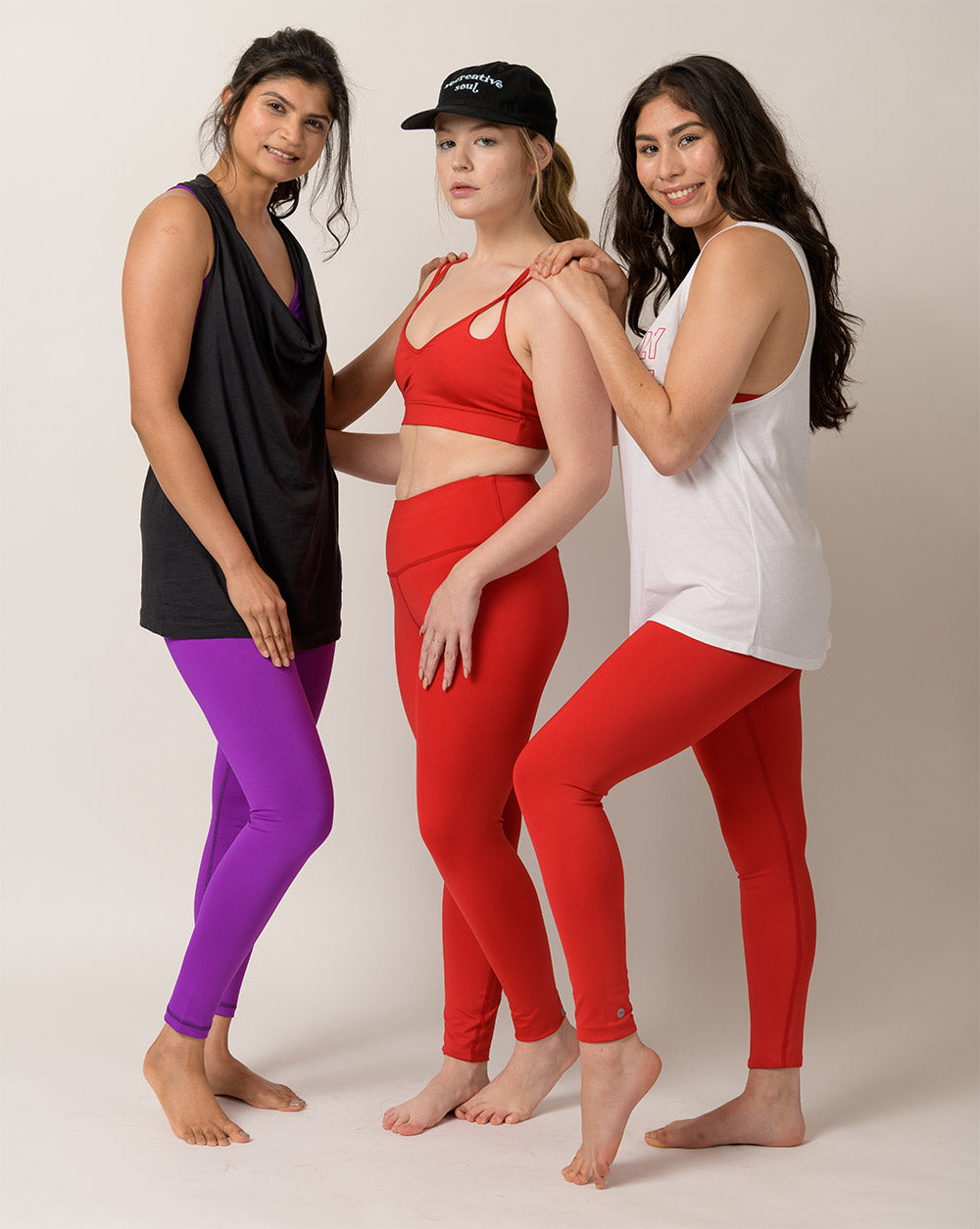 three women wearing Recreative Apparel colorful leggings and bras made with recycled polyester fabric