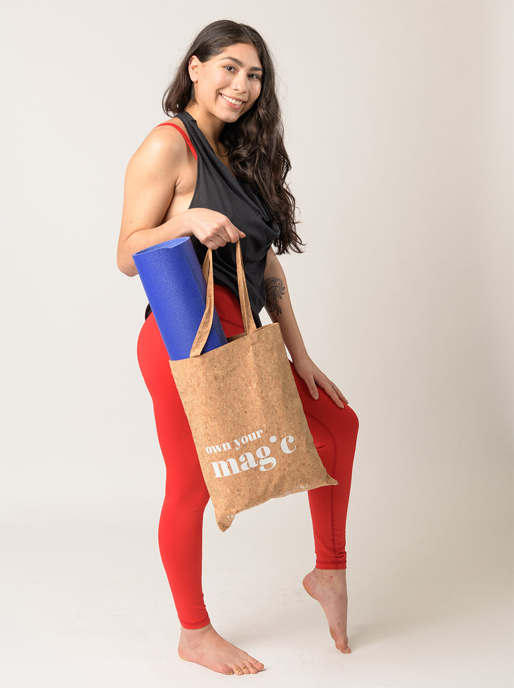 woman wearing Recreative Apparel leggings in fire red and carrying a yoga mat in a reusable vegan cork tote bag