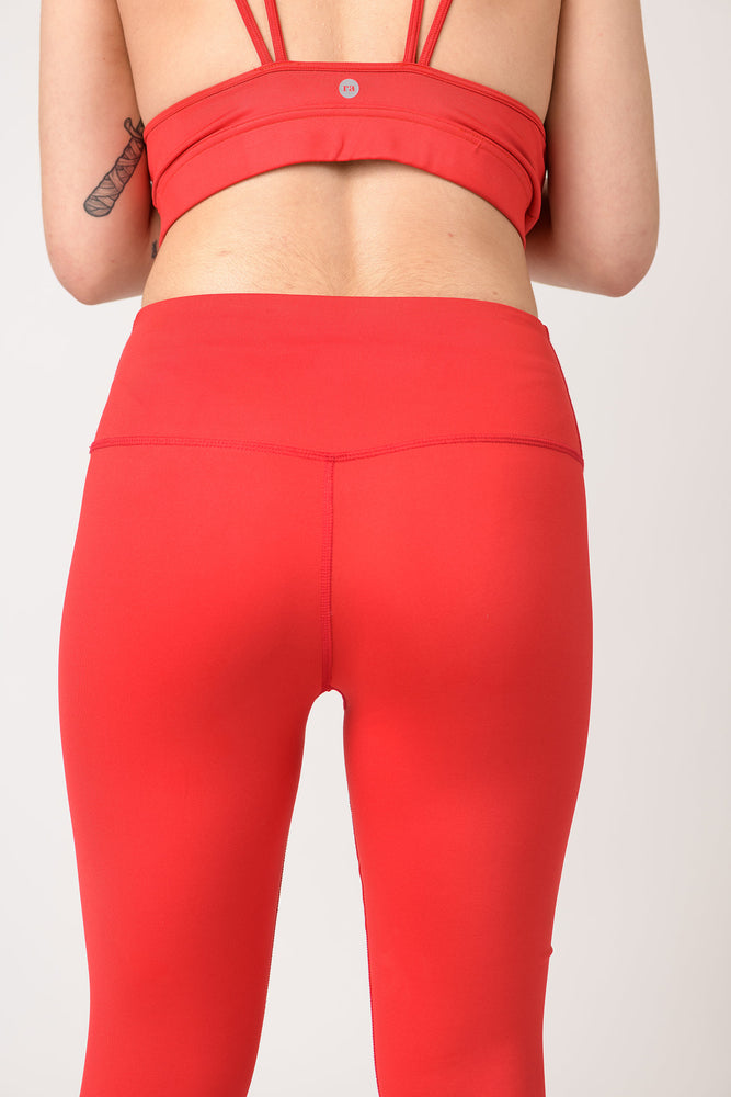 back view of a woman wearing Avalon high waist leggings in fire red