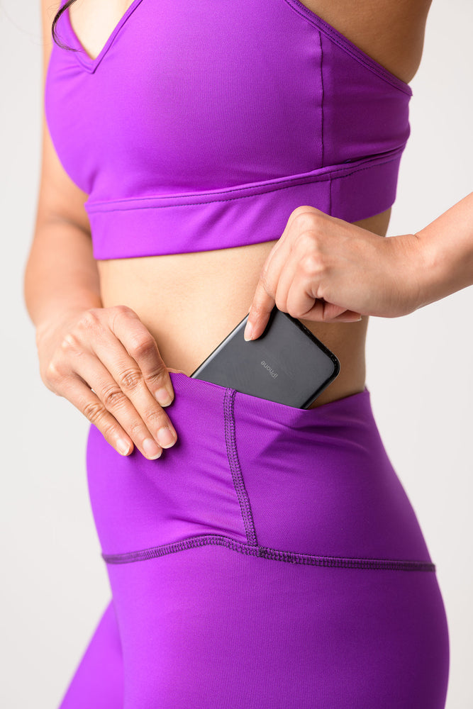 woman wearing Avalon high rise leggings in deep purple placing a cell phone inside pocket