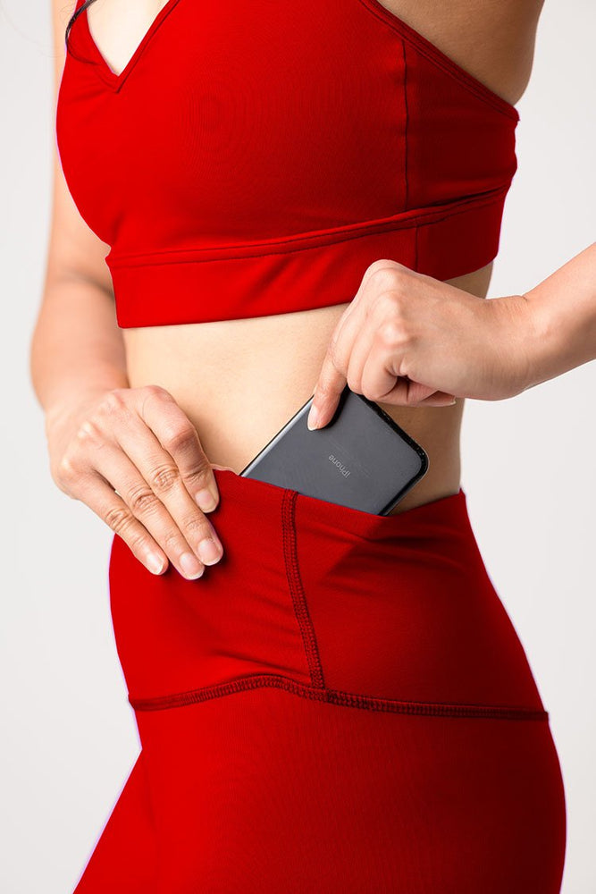 woman wearing Avalon high waist leggings in fire red placing cell phone inside pocket