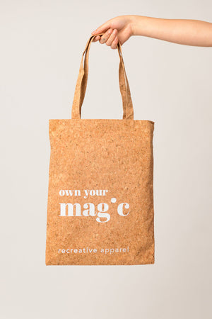 a person holding a reusable tote bag with inspiring quote