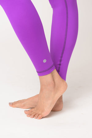 woman wearing Avalon high rise leggings in deep purple with reflective logo