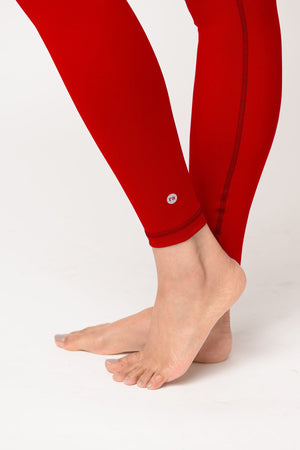 woman wearing Avalon high waist leggings in fire red with reflective logo
