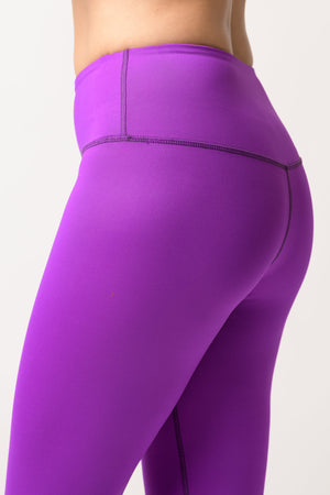 woman wearing Avalon high rise leggings in deep purple side view