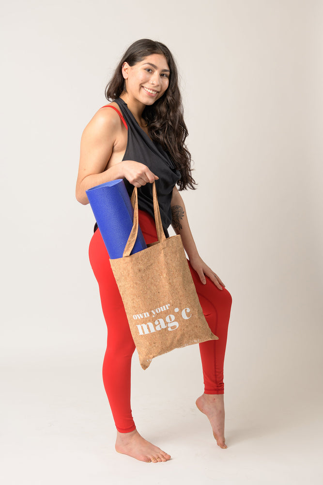 smiling woman wearing red leggings and carrying reusable cork tote bag