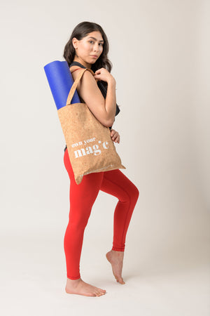 woman in red leggings carrying reusable tote bag with yoga mat