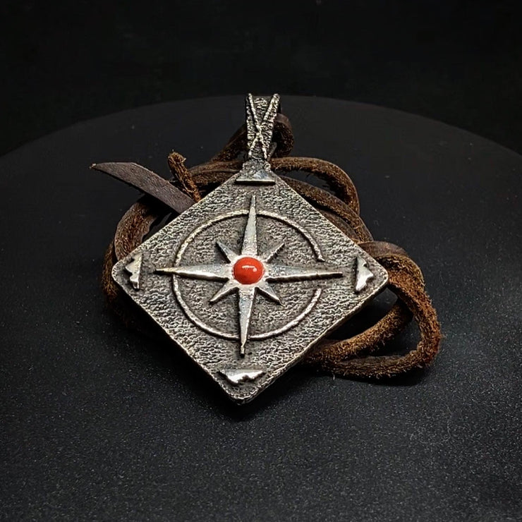 A Sterling Silver pendant sits on a table with a leather necklace folded up under it. The Pendant is diamond shaped with a Diné Circle of Life design and a red coral stone at the center.