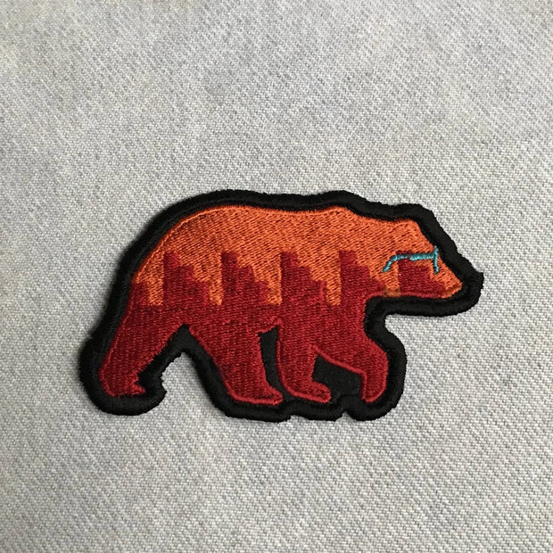 Naasgó, forward movement, embroidered patch collaboration with Corey Begay, a walking bear with orange and red body and blue glasses with a black embroidered edge.