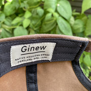"Detail image of the brand tag in the hat band. Tag text says ""Ginew Native American Owned Portland, ORE - USA"""