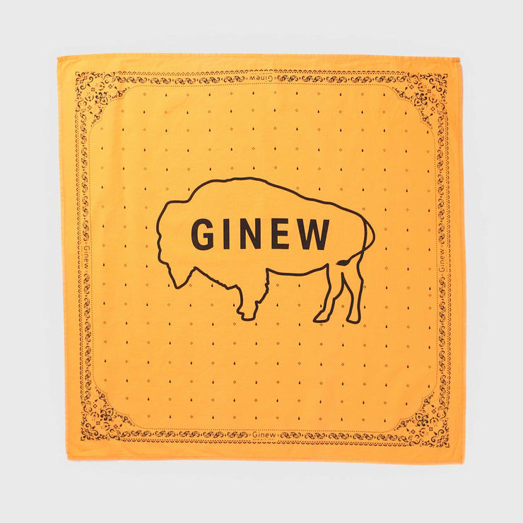 "A picture of a bandana laying on a cream background. The fabric of the bandana is golden-yellow and the design on the bandana is printed in black ink. The design includes flowers and decorative shapes around the edge and an outline of a buffalo and the word ""Ginew"" in the middle."