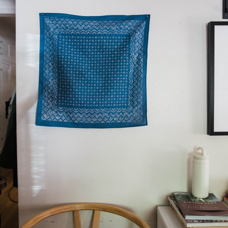 The Indigo Medel Bandana hangs on a wall of house next to a framed picture and above a chair and a table with books and a water bottle.