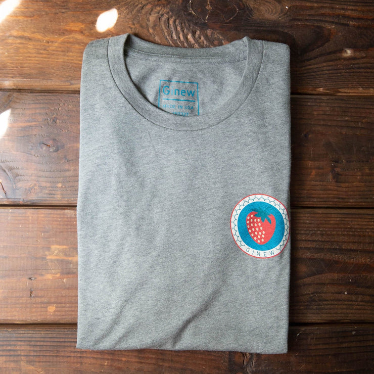 A photo of a t-shirt folded on a wooden picnic table. The shirt is light heather grey with design of a strawberry in the upper left chest position. The Strawberry is red against a turquoise background with a white ring around it.