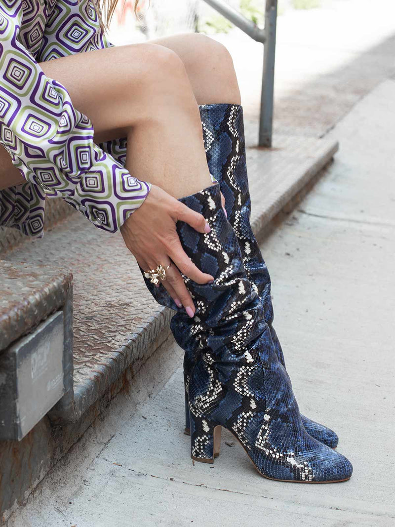 Woman wearing a pair of Mavette Savona Boots Knee High Blue Snake Print while sitting on stairs