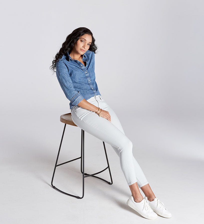 Woman sitting on chair wearing white jeans