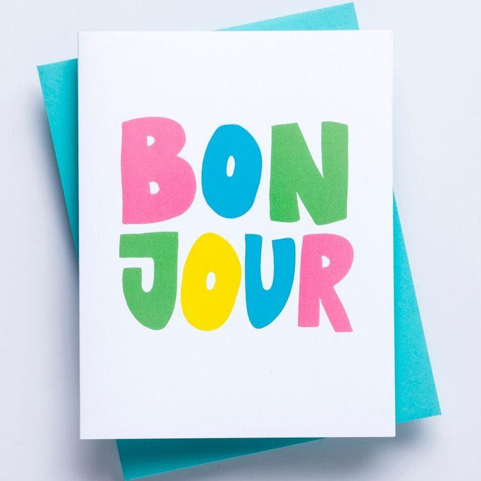A white greeting card with the word 'Bonjour' displayed on the face in multicolored lettering with a blue enveloped