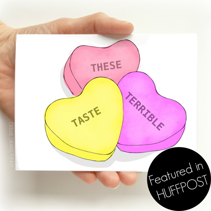 A white Valentine's day greeting card with images of three sweet Valentine's day candy hearts in colors of red, pink, and yellow and the words 'these' 'taste' 'terrible'