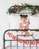 Cream Yarn Pom Poms strung at the end of a child's bed complimenting Christmas holiday décor