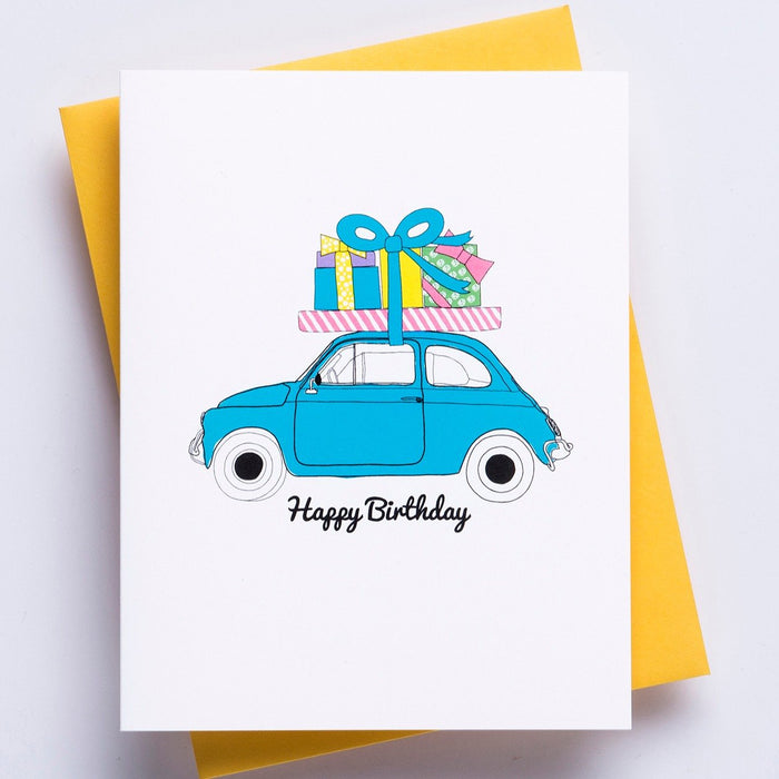 Happy Birthday Moto Greeting Card - A white greeting card with a image of a small car carrying birthday gifts on the roof and the words 'happy birthday' accompanied by a bright yellow envelope.