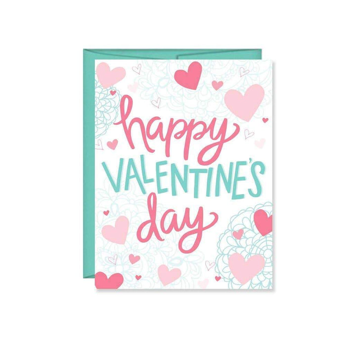 A traditional happy valentines day greeting card set on white paper with hearts and the words 'happy valentines day' accompanied by a teal colored envelope.