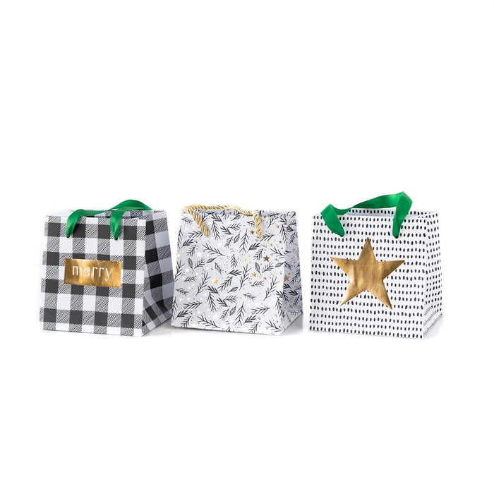 Holiday Mini Gift Bags in cute holiday designs such as black and white plaid, white with holiday style foliage, and white with black polka dots and a gold star.