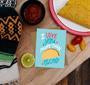 I love you more than tacos card displayed on a table with other party favors