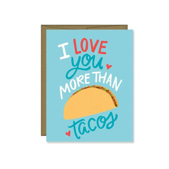 A silly card set on blue card stock with an image of a taco and the words 'I love you more than tacos' imprinted on the face with a few hearts