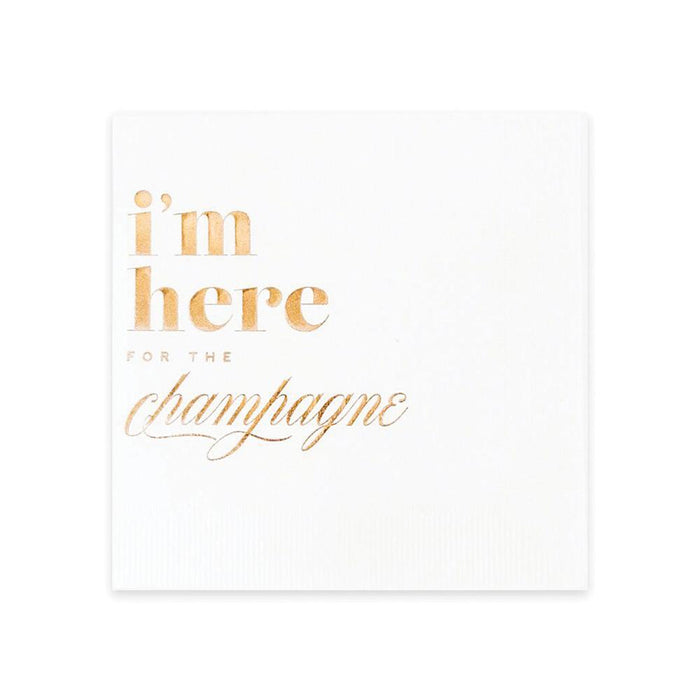 A white cocktail napkin with the words 'I'm here for the champagne' imprinted in rose gold foil