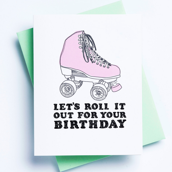 A white birthday card with an image of a roller skate and the words 'let's roll it out for your birthday' displayed over a green envelope and white background