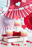 Cupcakes made with the valentine's day cupcake kit surrounded by Valentine's themed decorations