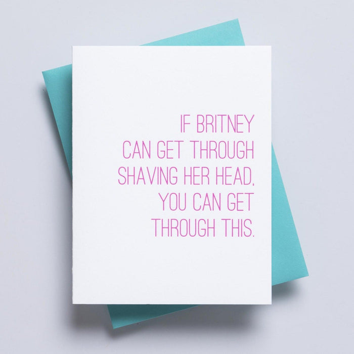 A simple white greeting card accompanied by a blue envelope and pink text on the face of the card reading 'if britney can get through shaving her head, you can get through this'.