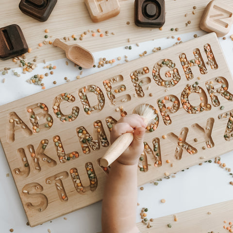Wooden alphabet tracing board with a child filling in with sensory materials like rice and beans for sensory play.
