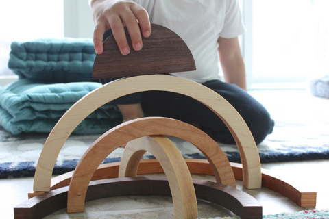 Little boy playing with organic all natural wooden stacker rainbow and creating new patterns.