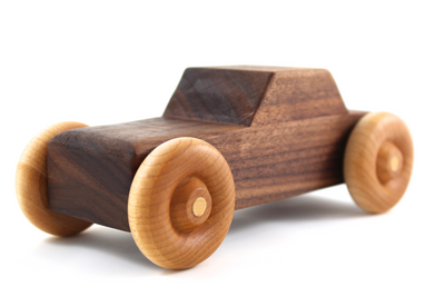 Children's wooden organic push toy car made out of a dark hardwood.