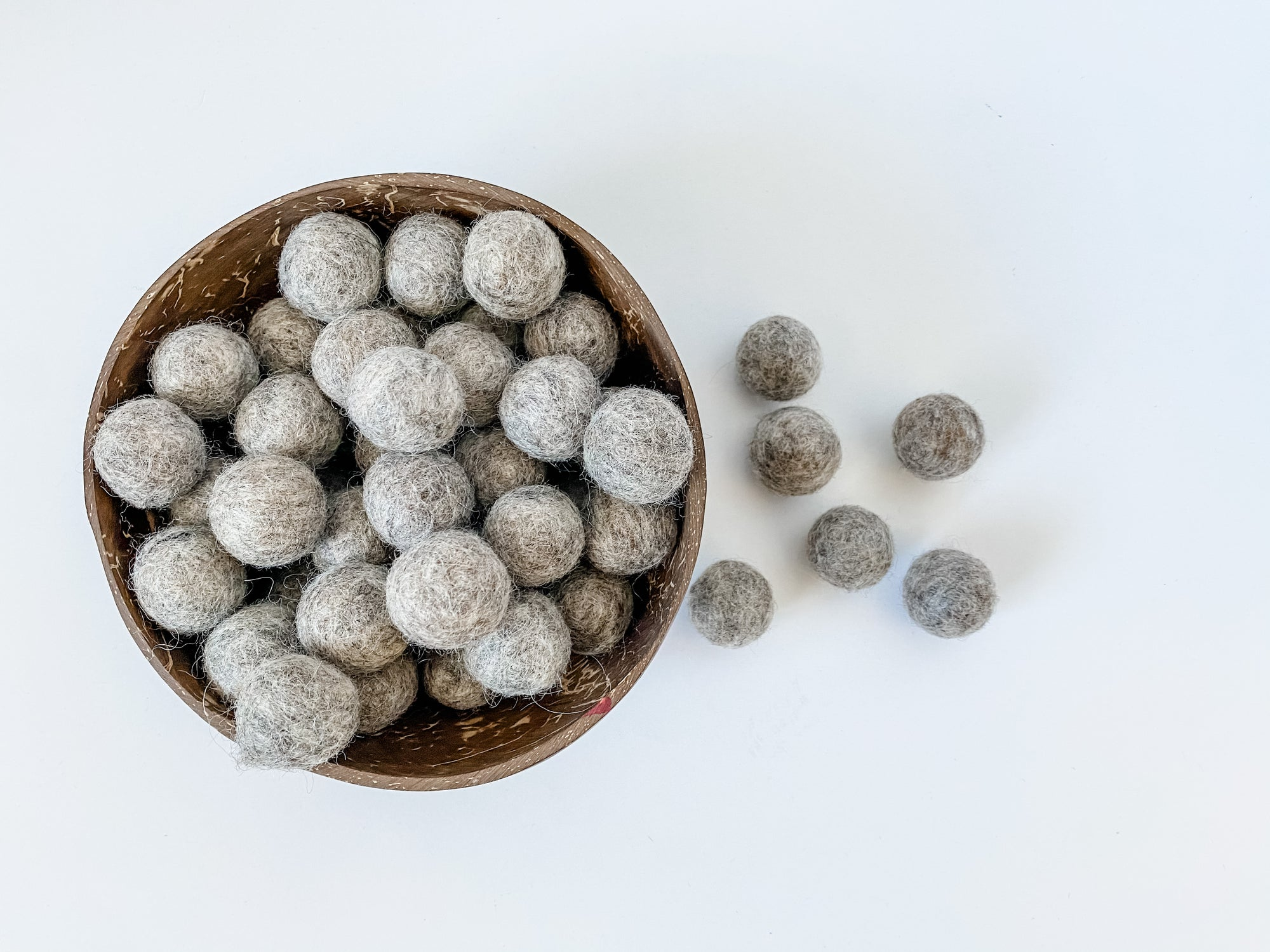 Fat and chunky gray wool balls for sensory play tray ideas and for use as math counters.