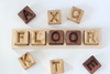 Five frame word learning board spelling out floor with wooden alphabet letters.